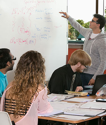 students around a table with someone pointing to whiteboard