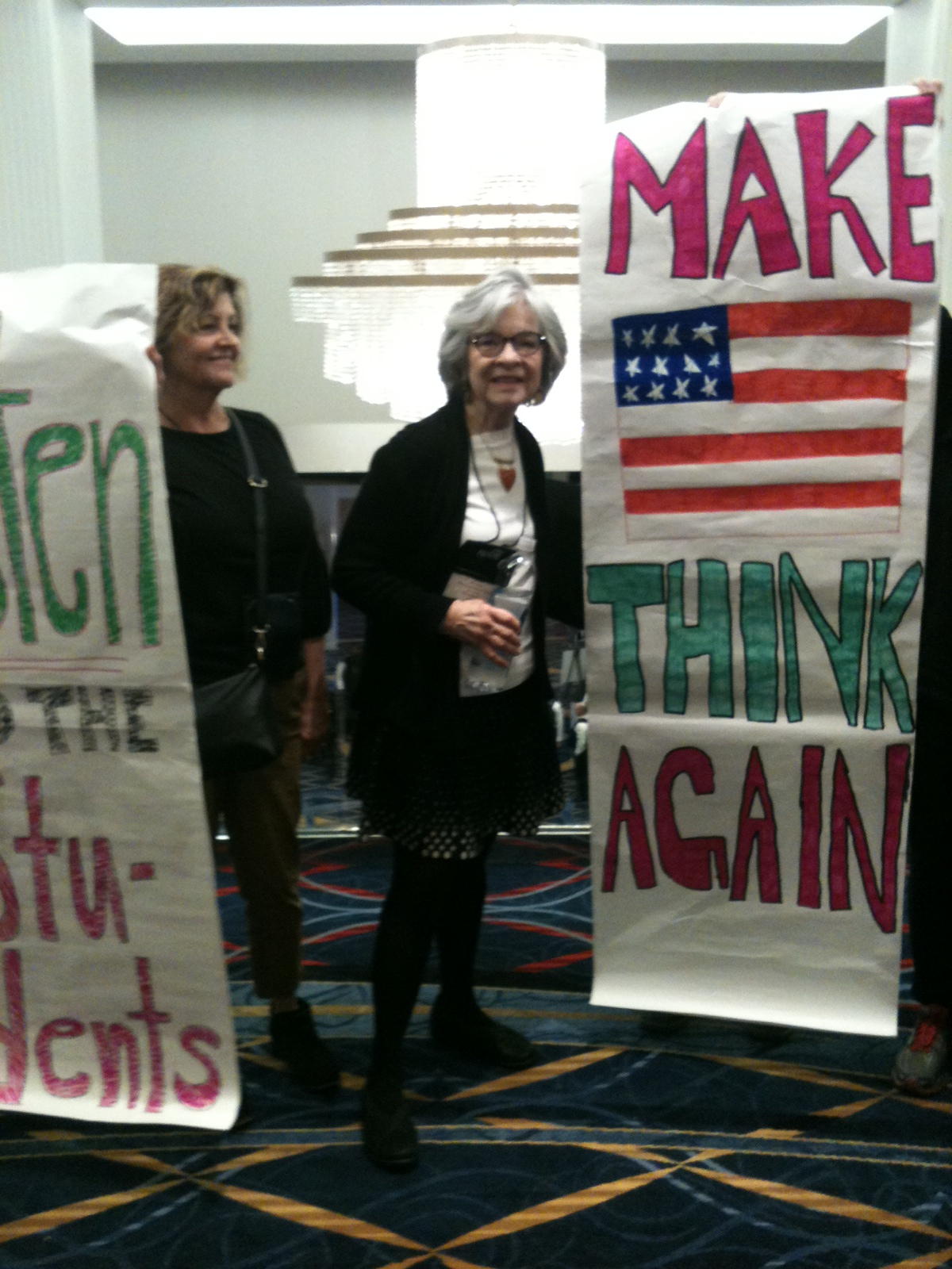 "Effie Russell holding a poster that reads ""make america think again."""