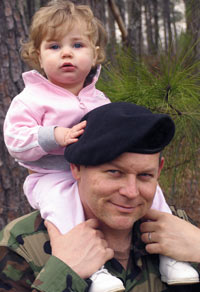 soldier carrying his toddler daughter on his back